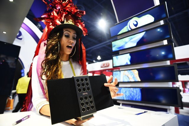 Benq repesentative Patoria Hardy displays the treVolo electrostatic portable Bluetooth speaker, January 6, 2015 at the Consumer Electronics Show in Las Vegas, Nevada. The speakers, which folds shut for easy packing, retails for USD $299. (Photo by Robyn Beck/AFP Photo)