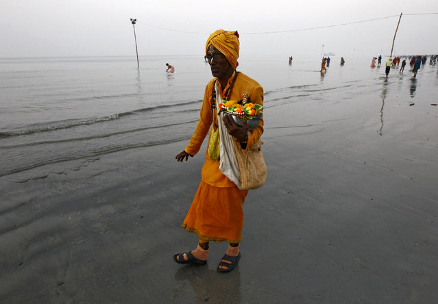 "A ""Sadhu"", or a Hindu holy man, carries an idol of a Hindu deity as he walks along the confluence of the river Ganges and the Bay of Bengal, ahead of the ""Makar Sankranti"" festival at Sagar Island, south of Kolkata January 13, 2015. (Photo by Rupak De Chowdhuri/Reuters)"