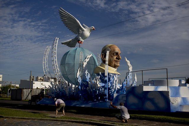 The Ara Yevi samba school put the finishing to touches on one of their floats, decorated with Pope Francis, before the carnival parade in Gualeguaychu, Argentina, Saturday, January 10, 2015. This one of four floats that pays tribute to the Pope, highlighting his arrival to the Vatican, his love for soccer and tango dance, and his work with the poor. (Photo by Natacha Pisarenko/AP Photo)