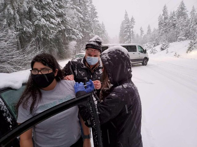 Josephine County Public Health staff and volunteers administer COVID-19 vaccinations to stranded motorists after returning from a clinic with unused doses and getting stuck in a snowstorm on Highway 199 in Hayes Hill, Oregon, January 26, 2021. (Photo by Josephine County Public Health/via Reuters)