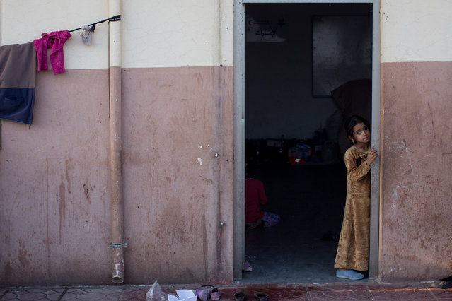 A young girl waits at a food distribution center at an IDP camp in Debaga on November 6, 2016 in Debaga, Iraq. The camp is full to capacity, housing almost 35,000 people from the surrounding areas of Mosul and Al Qayyahh, in the past two days the camp has taken in close to 1500 new arrivals as people flee the ongoing Mosul offensive. (Photo by Chris McGrath/Getty Images)
