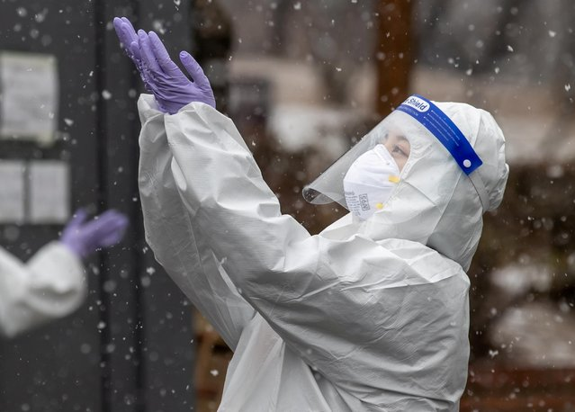 A health worker wearing a protective suit enjoys the falling snow at a coronavirus testing site in Seoul, South Korea on January 12, 2021. (Photo by Yonhap via Reuters)
