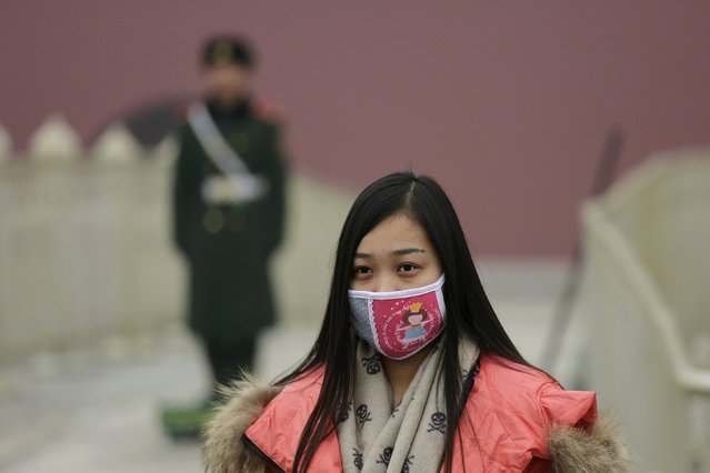 "A women wearing a mask to protect from extreme smog visits the Tiananmen Gate in Beijing December 8, 2015 as China's capital issues its first ever ""red alert"" for pollution. (Photo by Damir Sagolj/Reuters)"