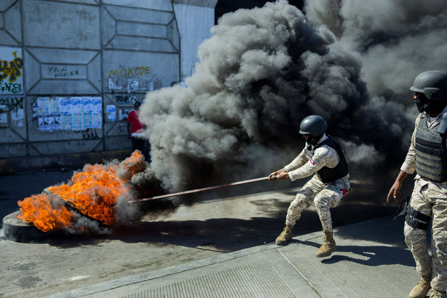 Police try to put out a burning barricade during a demonstration demanding the resignation of President Jovenel Moise, in Port-au- Prince, Haiti, Friday, January 15, 2021. Moise has one more year in power, but a growing groundswell of opposition is organizing protests and demanding he resign next month amid spiraling crime, a crumbling economy and approval of what critics say are illegal presidential decrees and unconstitutional moves, worrying many that Moïse is amassing too much power as he enters his second year of rule by decree. (Photo by Joseph Odelyn/AP Photo)