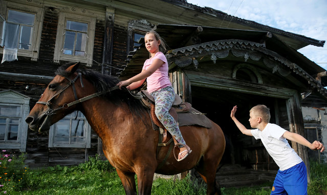 Children play with a horse near a historic house in the village of Cherevkovo, Arkhangelsk region, Russia, July 12, 2016. Picture taken July 12, 2016. (Photo by Maxim Shemetov/Reuters)