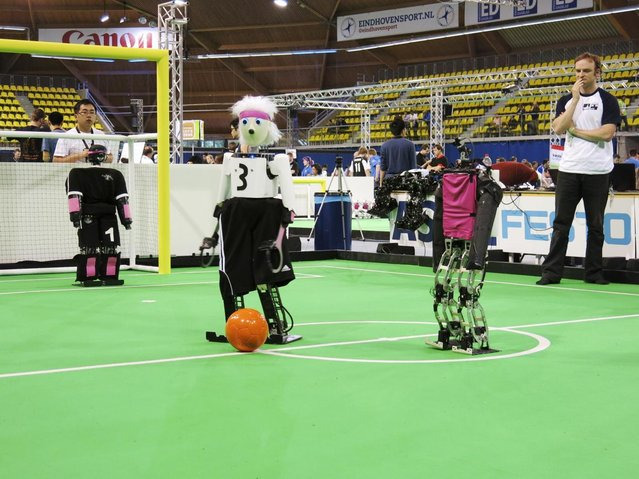 In this photo taken Thursday, June 27, 2013, a robot from the University of Bonn dribbles around a Japanese competitor at the RoboCup championships in Eindhoven, Netherlands. Around 300 teams from 40 countries are competing this week at the RoboCup. The competition has the long-term goal of building a team of androids good enough to beat the human world cup team by 2050. (Photo by Toby Sterling/AP Photo)