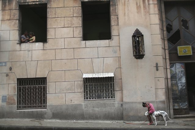 A child plays with a dog in downtown Havana, January 20, 2015. (Photo by Alexandre Meneghini/Reuters)