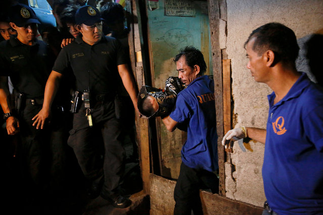 Funeral parlour workers carry a body out of a house in Manila, Philippines early November 1, 2016. (Photo by Damir Sagolj/Reuters)