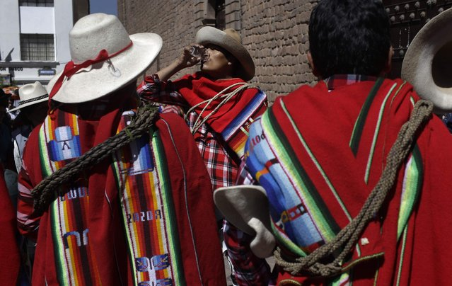 Dancers drink beer while they prepare to perform an ancestral Inca dance in Cuzco, Peru, Saturday, June 23, 2018. June is full of festivities throughout the region of Cuzco, culminating on June 24 with the Inti Raymi, the Festival of the Sun. (Photo by Martin Mejia/AP Photo)