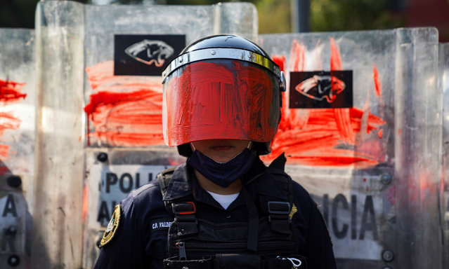 A riot police officer is seen after her helmet visor was painted red by a member of a feminist collective during a protest against gender and police violence, in Mexico City, Mexico on November 11, 2020. (Photo by Toya Sarno Jordan/Reuters)
