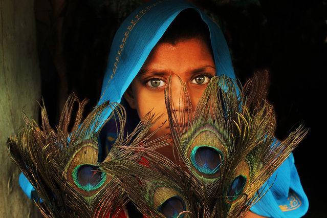 """The peacock girl"". This little girl was with feathers of peacock. Location: Kalyani, West-Bengal. (Photo and caption by Sanghamitra Sarkar/National Geographic Traveler Photo Contest)"