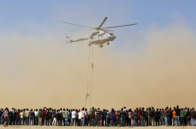 Spectators watch Indian Air Force (IAF) soldiers performing during an awareness drive in the western Indian city of Ahmedabad, January 17, 2015. The drive is aimed at motivating young people to join the Indian armed forces. (Photo by Amit Dave/Reuters)