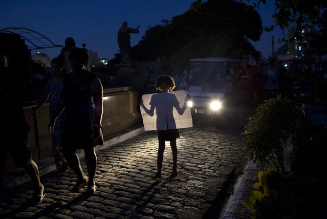 In this Thursday, June 21, 2018 photo, a girl holds a sign protesting the death of 14-year-old Marcos Vinicius da Silva, as she is illuminated by the headlights of the vehicle transporting the coffin containing his remains at a cemetery in Rio de Janeiro, Brazil. Da Silva is one of two teenagers killed the previous day by stray bullets in Rio de Janeiro. (Photo by Silvia Izquierdo/AP Photo)
