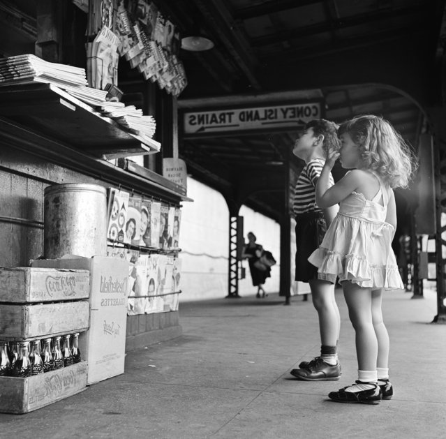 A brother and his sister look up at a newsstand, located on the platform of the New York city subway, as they wait for the train to Coney Island, New York, 1948. (Photo by Getty Images)