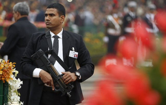 An Indian security officer guarding India's Prime Minister Narendra Modi and U.S. President Barack Obama keeps his weapon at the ready as he watches the crowd at the Republic Day parade in New Delhi January 26, 2015. (Photo by Jim Bourg/Reuters)