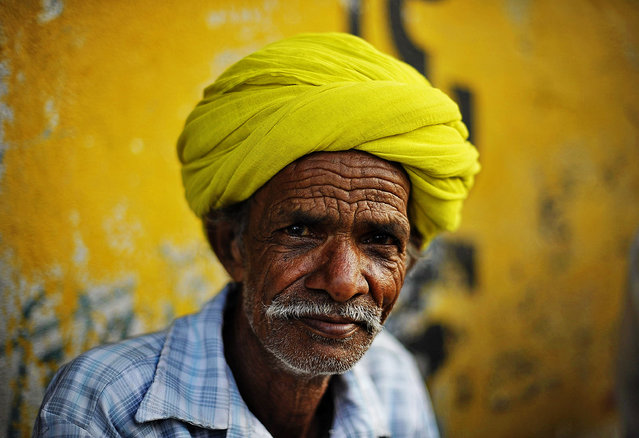 """Portrait of man in a citron green turban"". Rajasthan is widely recognized for its charming and elegant colourful turbans. I saw this Local man sitting on the street, he wearing a citron green turban, the colour blended into background painted wall. I thought it's nice, took this shot. Location: Udaipur, Rajasthan, India. (Photo and caption by Xuesong Liao/National Geographic Traveler Photo Contest)"