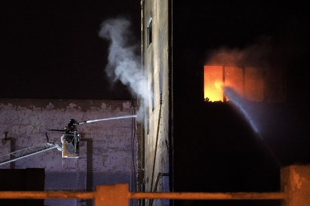 Firefighters work to extinguish a fire at a building in Badalona, Barcelona, Spain, Thursday, December 10, 2020. Authorities in northeastern Spain say a fire has raged through an abandoned building occupied by squatters in the city of Badalona, injuring at least 17 people, including two in critical condition. Firefighters say they rescued around 30 people from windows as the building burned late Wednesday. (Photo by Joan Mateu/AP Photo)