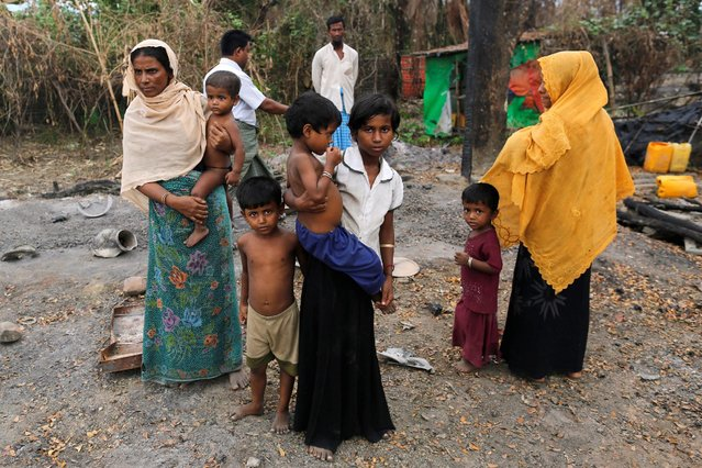 A family stands beside remains of a market which was set on fire, in Rohingya village outside Maungdaw, in Rakhine state, Myanmar October 27, 2016. (Photo by Soe Zeya Tun/Reuters)