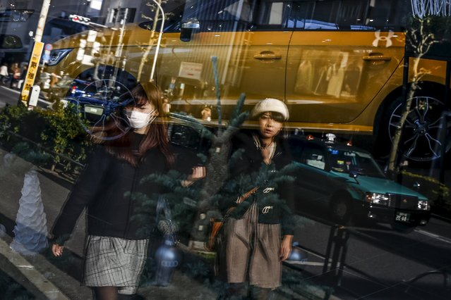 Women are reflected in the window of a car dealer as they walk in a shopping district in Tokyo, Japan, December 25, 2015. Japan's core consumer prices rose for the first time in five months in November, but household spending tumbled, casting doubt on the central bank's view that robust consumption will help accelerate inflation to its 2 percent target. (Photo by Thomas Peter/Reuters)