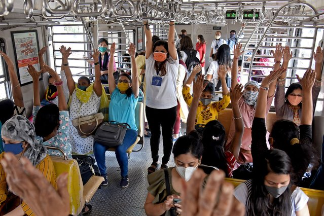 A yoga instructor (C) guides female passengers exercise while commuting on the ladies compartment of a local train in Mumbai on March 8, 2021 on the International Women's Day. (Photo by Sujit Jaiswal/AFP Photo)
