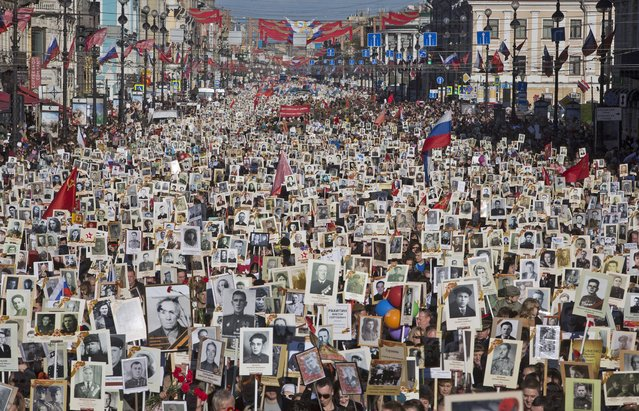 Local residents carry portraits of their ancestors, participants in World War Two as they celebrate the 70th anniversary of the defeat of the Nazis in World War II in St. Petersburg, Russia, May 9, 2015. About 100,000 people walked in central streets in a march named 'Immortal Regiment' while carrying portraits of their relatives who fought in World War Two. (Photo by Dmitry Lovetsky/AP Photo)