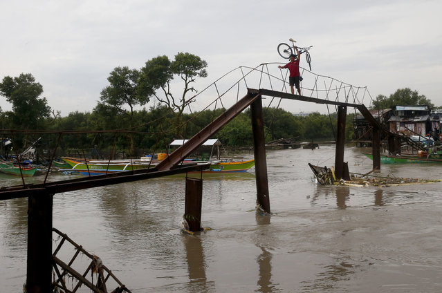 A man carries his bicycle on a narrow footbridge over a swollen river from monsoon rains brought on by a tropical storm for the second day Wednesday, July 18, 2018, in Bacoor, south of Manila, Philippines. Floodwaters have receded Wednesday in Manila but local authorities still suspended classes as well as some work in Government offices. (Photo by Bullit Marquez/AP Photo)