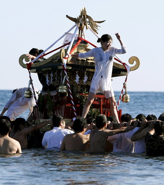 "A woman riding on a ""mikoshi"" or portable shrine cheers on people as they carry it into the sea during a festival to wish for calm waters in the ocean and good fortune in the new year in Oiso, Kanagawa prefecture, west of Tokyo, Japan, January 1, 2016. (Photo by Yuya Shino/Reuters)"