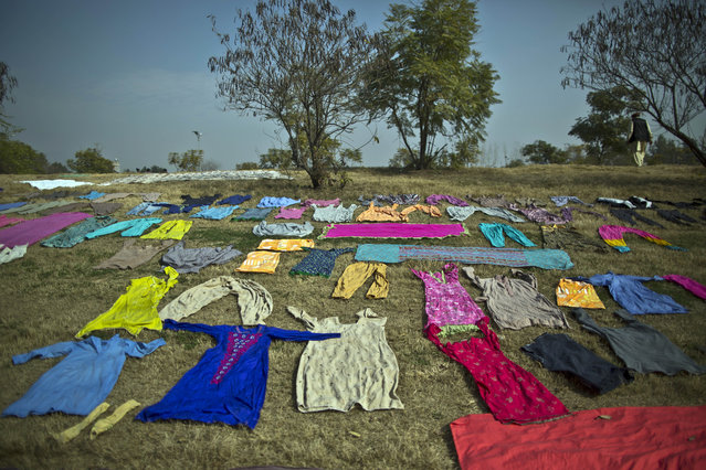 A Pakistani man walks past laundry left on a roadside to dry, in Islamabad, Pakistan, Saturday, January 31, 2015. (Photo by Muhammed Muheisen/AP Photo)