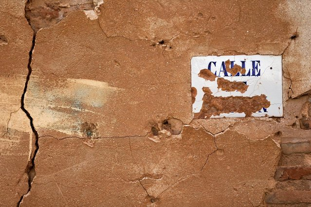 Bullet holes and the remains of a street sign are seen on a building in the old village of Belchite, in northern Spain, November 13, 2016. (Photo by Andrea Comas/Reuters)
