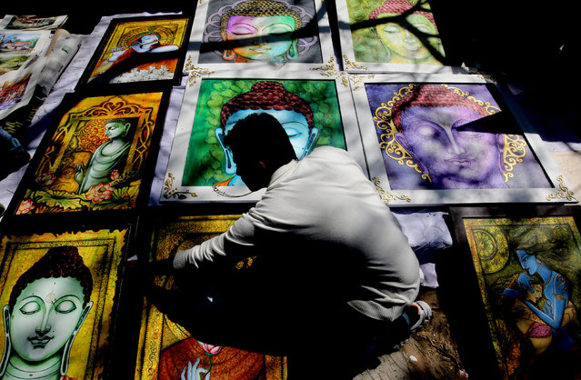 An Indian artist arranges artworks at the 13th annual 'Chitra Santhe' or 'Art Fair' organised by Karnataka Chitrakala Parishath in Bangalore, India, January 3, 2016. The one day event gives the opportunity to the local artists to showcase and sell their artworks to the public. (Photo by Jagadeesh N.V./EPA)