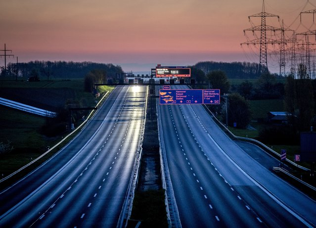 An almost empty highway is seen shortly after the end of the curfew in Frankfurt, Germany, Sunday, April 25, 2021. From the weekend on a curfew becomes effective to avoid the outspread of the coronavirus. (Photo by Michael Probst/AP Photo)