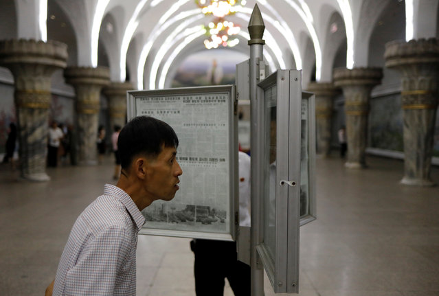 Commuters read newspapers displayed at a subway station in Pyongyang, North Korea on September 11, 2018. (Photo by Danish Siddiqui/Reuters)