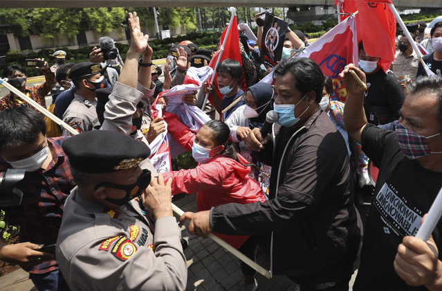Activists scuffle with police officers as they are dispersed during a rally against Myanmar's military coup near the Association of Southeast Asian Nations (ASEAN) Secretariat ahead of a leaders' meeting in Jakarta, Indonesia, Saturday, April 24, 2021. Southeast Asian leaders are to meet Myanmar's top general and coup leader in an emergency summit in Indonesia Saturday, and are expected to press calls for an end to violence by security forces that has left hundreds of protesters dead as well as the release of Aung San Suu Kyi and other political detainees. (Photo by Dita Alangkara/AP Photo)