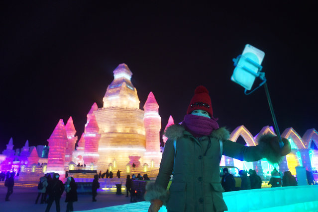 A woman uses a mobile phone to take a picture at the China Ice and Snow World during the Harbin International Ice and Snow Festival in Harbin, northeast China's Heilongjiang province on January 5, 2016. Over one million visitors are expected to attend the spectacular Harbin Ice Festival, where buildings of ice are bathed in ethereal lights and international ice sculptors compete for honours. (Photo by Wang Zhao/AFP Photo)