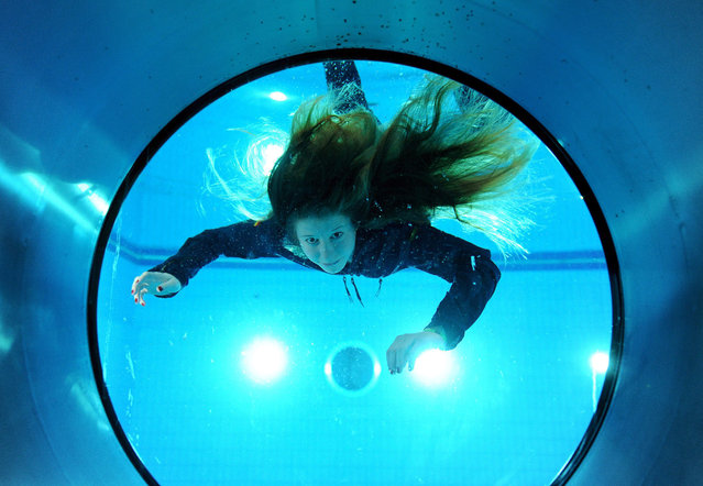 Christin Greisinger, prospective swimmer at the Marie Operations School swims in front of the porthole to the underwater observation at the German Marine's new rescue and water training hall in Bremerhaven, Germany, 17 February 2015. In a large pool the above water exit from a ditched helicopter, followed by scaling the rescue island is practiced. (Photo by Ingo Wagner/EPA)