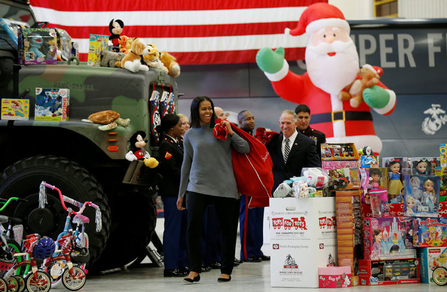 Carrying a sack full of toys, the U.S. First Lady Michelle Obama makes her annual visit to the Toys for Tots event at Joint Base Anacostia–Bolling in Washington, U.S. December 7, 2016. (Photo by Kevin Lamarque/Reuters)
