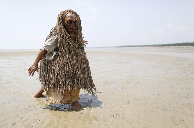 """Members of Malaysia's indigenous Mah Meri tribe perform the """"Main Jo-oh"""" dance during a """"Puja Pantai"""", a thanksgiving ritual to appease the spirits of the seas, in the village of Pulau Carey, outside Kuala Lumpur February 23, 2015. The Mah Meri tribe, who are descendants of seafaring people who lived off the sea through fishing and trading, celebrate their new year according to the lunar calendar, by making offerings to the sea. (Photo by Olivia Harris/Reuters)"""