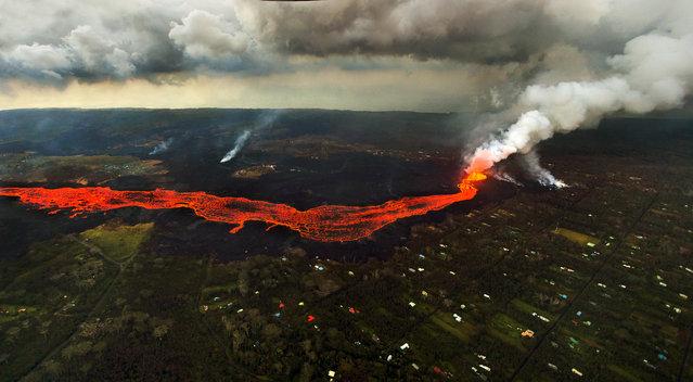 Lava from the Kilauea volcano flows in and around Pahoa, Hawaii, Sunday, June 10, 2018. (Photo by L.E. Baskow/AP Photo)