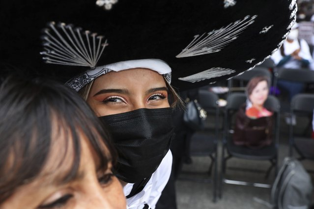 Wearing a mariachi hat, candidate Clara Brugada, who is running as a delegation leader under the ruling party Morena, smiles as she greets supporters on the last day of campaigning ahead of the June 6 mid-term elections, in the Iztapalapa borough of Mexico City, Wednesday, June 2, 2021. (Photo by Marco Ugarte/AP Photo)