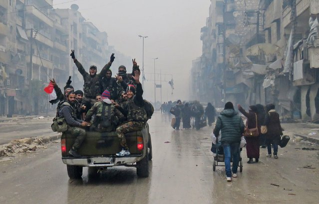 Syrian pro-regime fighters, gesture as they drive past residents fleeing violence in the restive Bustan al-Qasr neighbourhood, in Aleppo's Fardos neighbourhood on December 13, 2016, after regime troops retook the area from rebel fighters. Syrian rebels withdrew from six more neighbourhoods in their one-time bastion of east Aleppo in the face of advancing government troops, the Syrian Observatory for Human Rights said. (Photo by AFP Photo/Stringer)