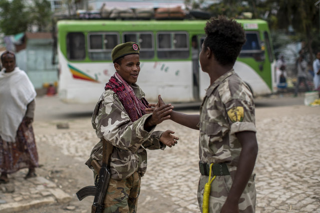 Fighters loyal to the Tigray People's Liberation Front (TPLF) greet each other on the street in the town of Hawzen, then-controlled by the group, in the Tigray region of northern Ethiopia, on Friday, May 7, 2021. The rural town is a microcosm of the challenge facing Prime Minister Abiy Ahmed – and a warning that the war here is unlikely to end anytime soon. (Photo by Ben Curtis/AP Photo)