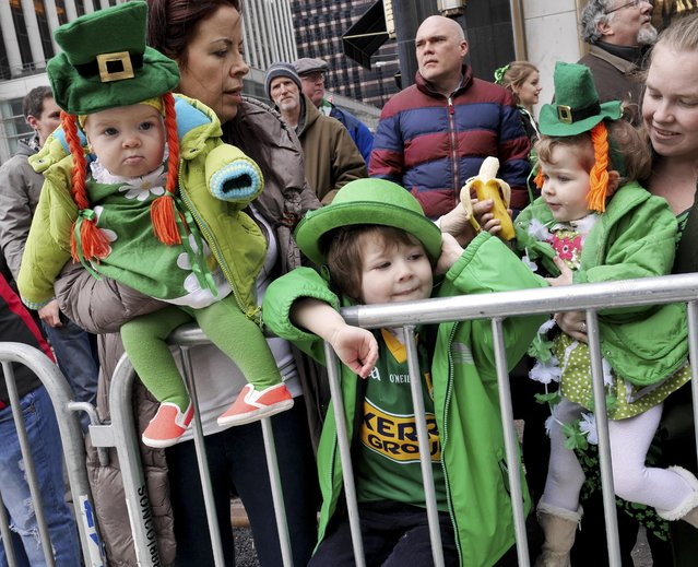 Auston O'Grady, 3, center, and his sisters Billie O'Grady, 7 months, right, and Zola O'Grady, 2, watch the St. Patrick's Day Parade in New York, Tuesday, March 17, 2015. (AP Photo/Seth Wenig)