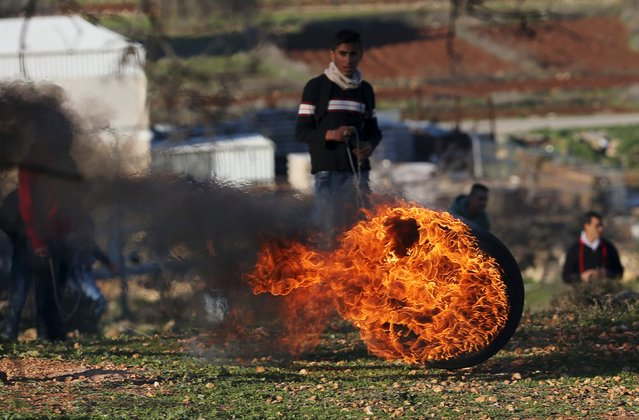 A Palestinian protester stands behind a burning tyre during clashes with Israeli troops, near Israel's Ofer Prison near the West Bank city of Ramallah December 25, 2015. (Photo by Mohamad Torokman/Reuters)