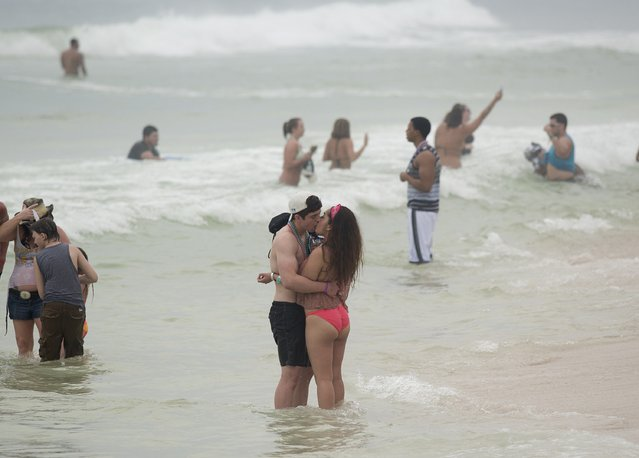 A couple kisses as they stand on the beach water during spring break festivities in Panama City Beach, Florida March 12, 2015. Unwilling to evict spring break, a crucial season in a community where tourism brings in more than $1 billion annually, the city has passed new rules to counter the worst excesses. (Photo by Michael Spooneybarger/Reuters)