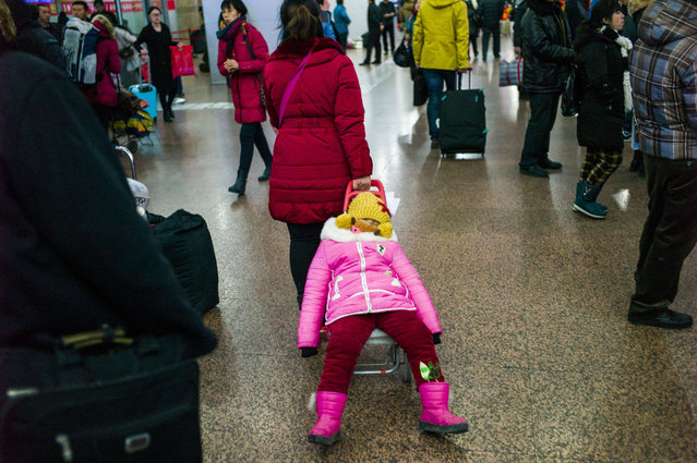 "A woman pulls her daughter in a trolley before taking their train to head to their hometown for the ""Spring Festival"" or Lunar New Year at Beijing Train Station on January 29, 2016. The Lunar New Year, this year being the Year of the Monkey on the Chinese zodiac, begins on February 8. (Photo by Fred Dufour/AFP Photo)"