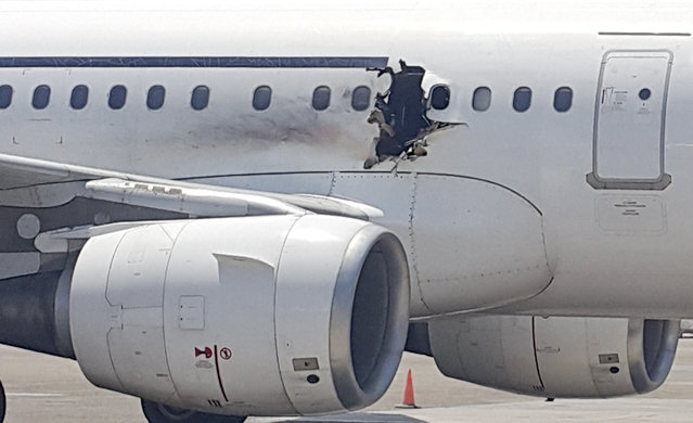 In this Tuesday, February 2, 2016 photo, a hole is photographed in a plane operated by Daallo Airlines as it sits on the runway of the airport in Mogadishu, Somalia. A gaping hole in the commercial airliner forced it to make an emergency landing at Mogadishu's international airport late Tuesday, officials and witnesses said. (Photo by AP Photo)