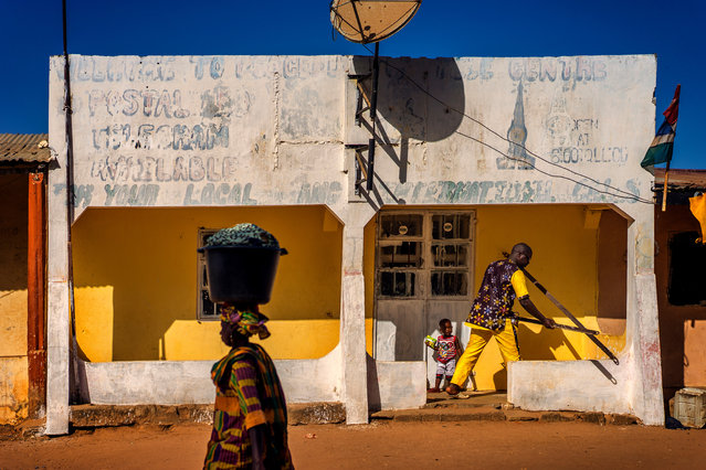 """""""My friend Sana opening his pharmacy in Banjul, the Gambia. I loved the symmetry of the scene, broken by Sana, his son and the lady"""". (Photo by Steve Baker/The Guardian)"""