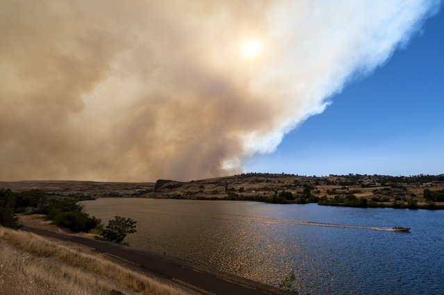 A boat heads down the Snake River as smoke from the Asotin Complex Fire west of Clarkston, Wash., wafts eastward into Lewiston, Idaho on Wednesday, July 7, 2021. (Photo by Pete Caster/The Lewiston Tribune via AP Photo)