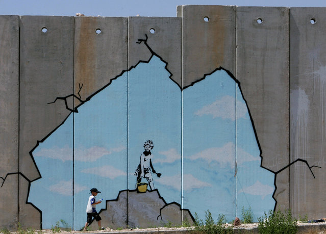 A Palestinian boy walks past a creation by Banksy along part of the controversial Israeli barrier near the Kalandia checkpoint in the West Bank in 2005. (Photo by Reuters/Stringer)