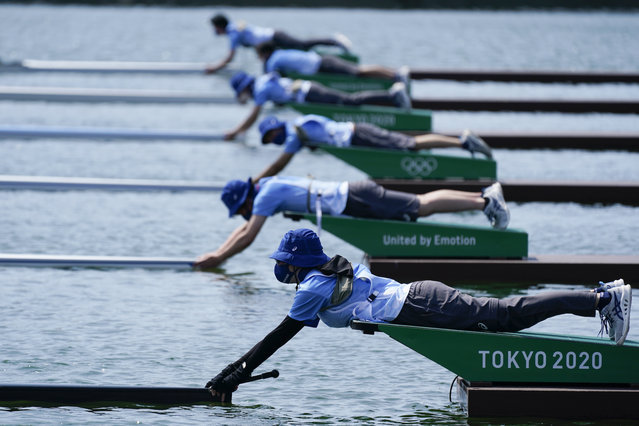 Volunteers holds the front of the sculls before a race in the women's single sculls at the 2020 Summer Olympics, Friday, July 23, 2021, in Tokyo, Japan. (Photo by Darron Cummings/AP Photo)
